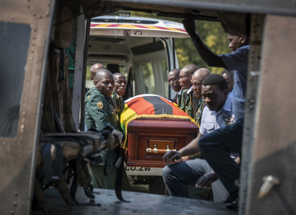 The casket of former president Robert Mugabe is carried by the presidential guard into an air force helicopter for transport to a stadium where it wil