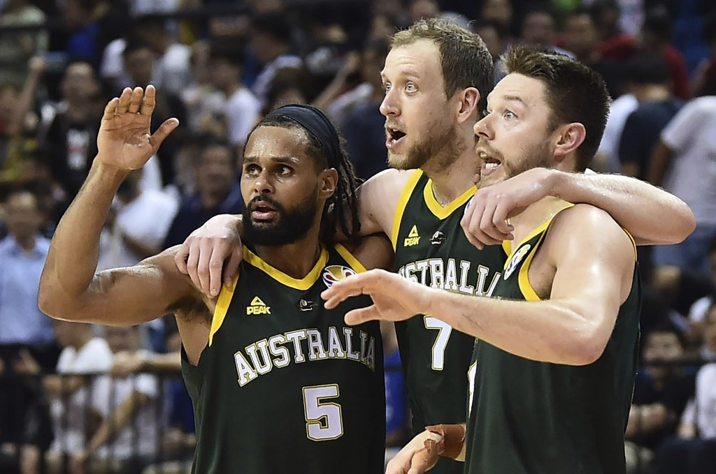 From left, Patty Mills, Joe Ingles and Matthew Dellavedova of Australia react during their second round basketball game against France in the FIBA Bas...