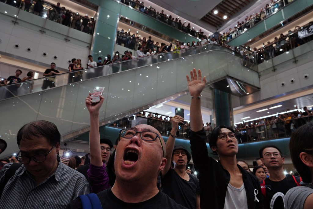 "Local residents sing a theme song written by protesters ""Glory be to thee"" at a shopping mall in Hong Kong Wednesday, Sept. 11, 2019. Hundreds of Hong"