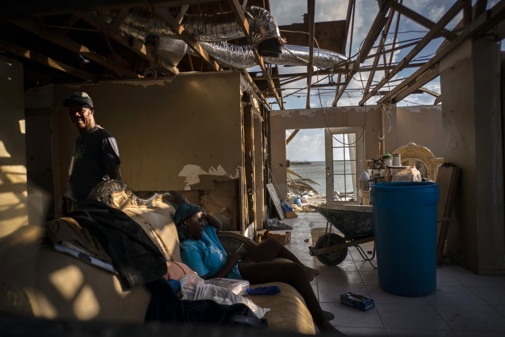 Phil Thomas, left, walks next to his daughter Ebony Thomas as she looks at her phone inside their home, shattered by Hurricane Dorian in Mclean's Town