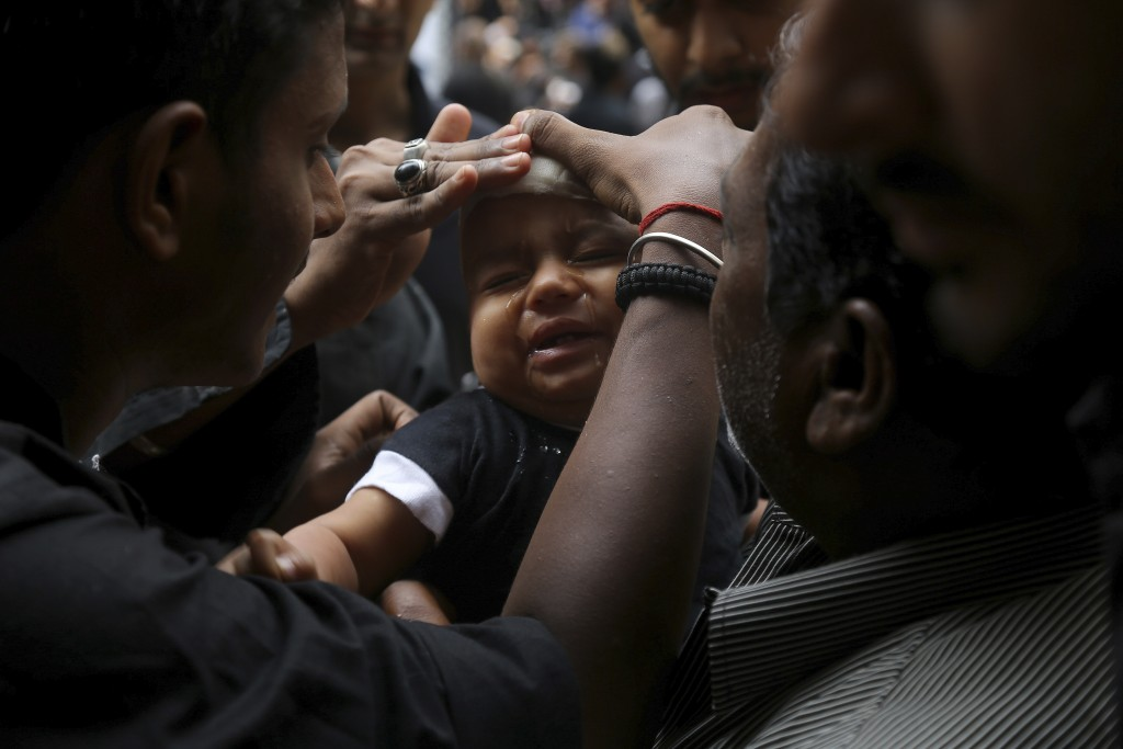 In this Tuesday, Sept. 10, 2019, file photo, Shiite Muslim child cries after he was given a cut on the forehead during an Ashoura procession in Hydera...