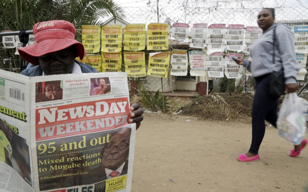 An ice cream vendor reads a newspaper on a street in Harare, Zimbabwe, Sept. 7, 2019. As controversy continues around the burial of Mugabe, the capita...