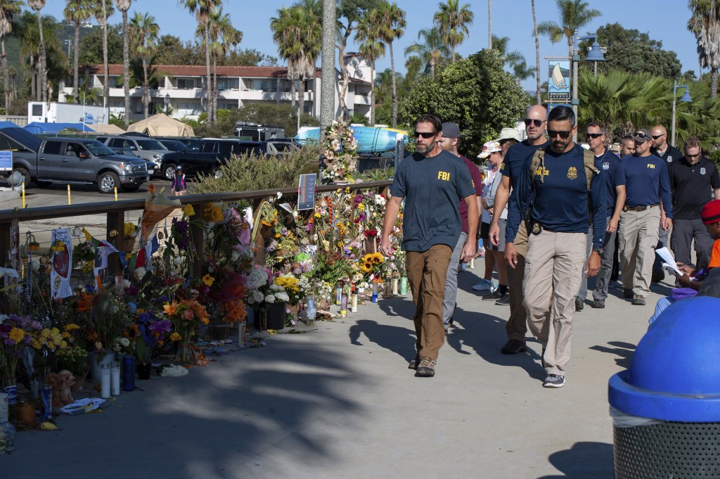 FBI agents walk past a memorial for the victims of the Conception dive boat on the Santa Barbara Harbor, as authorities issue a search warrant for the...