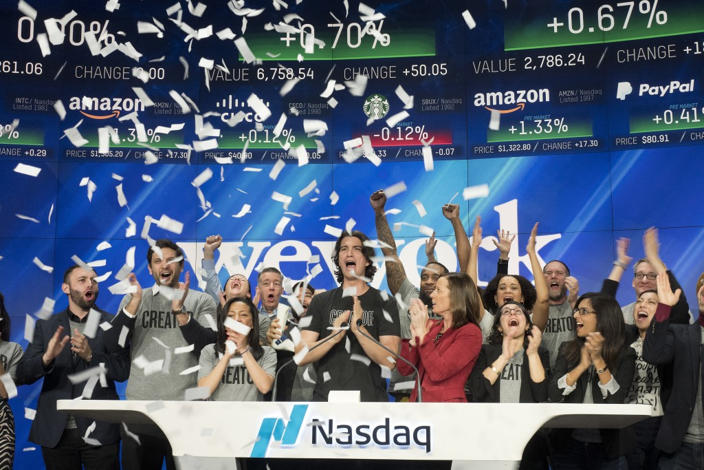 FILE - In this Jan. 16, 2018 file photo, Adam Neumann, center, co-founder and CEO of WeWork, attends the opening bell ceremony at Nasdaq in New York.