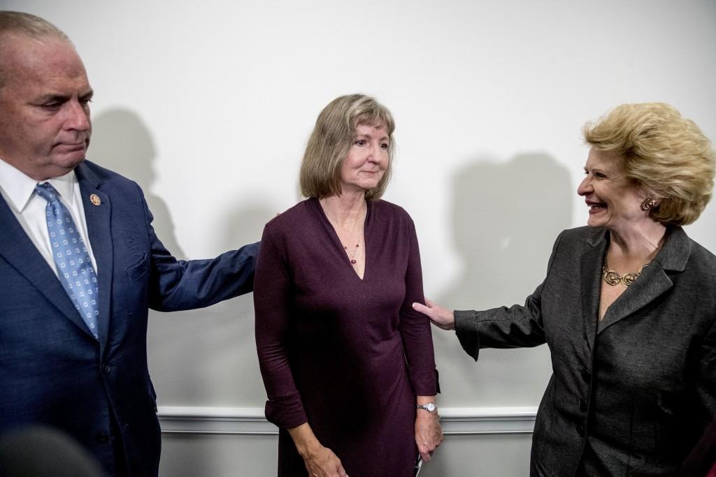Rep. Dan Kildee, D-Mich., left, Sen. Debbie Stabenow, D-Mich., right, and Elizabeth Whelan, the sister of Paul Whelan, center, speak following a news