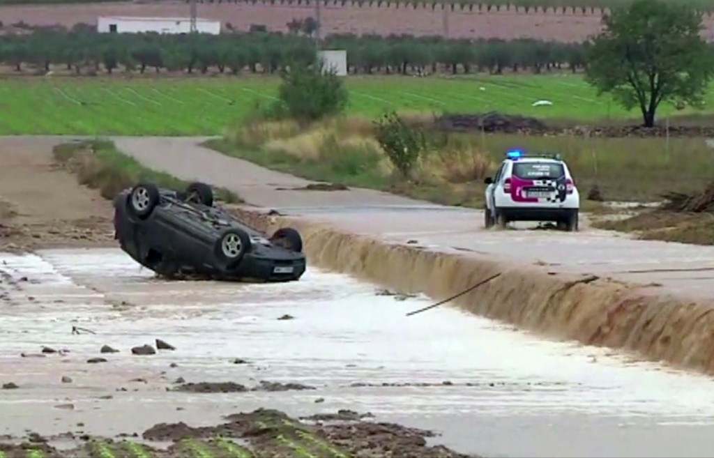 In this image made from video provided by Atlas, a police car drives to an overturned vehicle in which two people were drowned by floodwater, in Caude