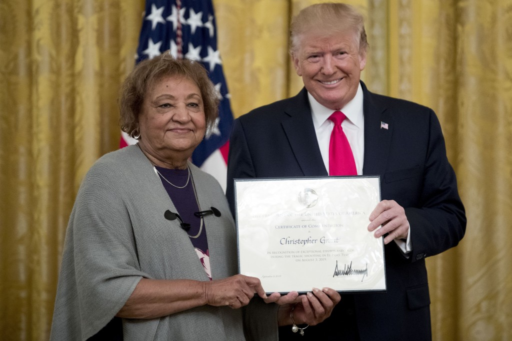 FILE - In this Sept. 9, 2019, file photo, President Donald Trump presents a Certificate of Commendation to Minnie Grant, the mother of Christopher Gra...
