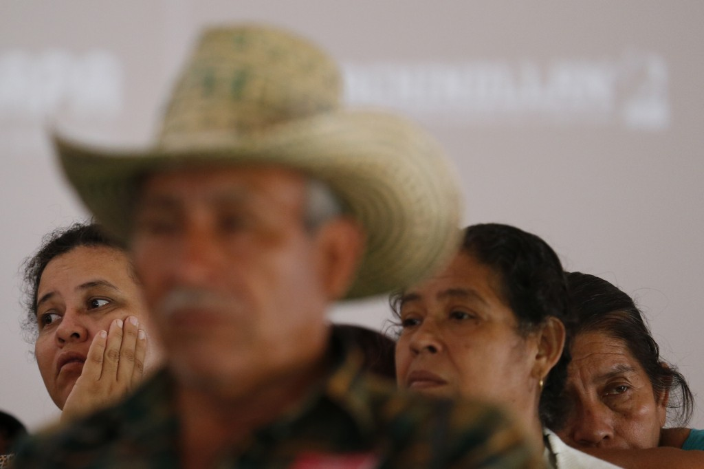 In this Sept. 11, 2019 photo, relatives of some of the 43 missing teacher's college students listen to other parents speak during a press conference f...