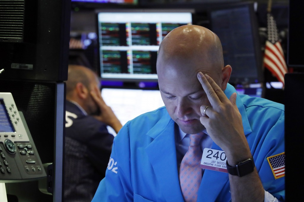 FILE - In this Aug. 23, 2019, file photo specialist Jay Woods, right, works on the floor of the New York Stock Exchange. The U.S. stock market opens a...