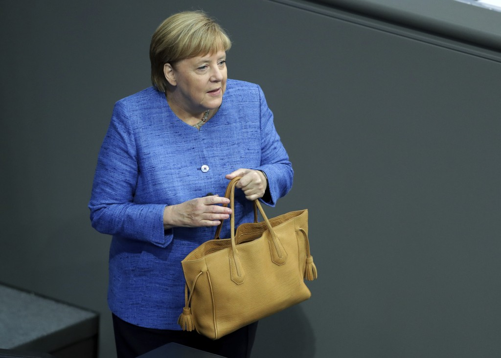 German Chancellor Angela Merkel holds her bag as she arrives for a meeting of the German federal parliament, Bundestag, at the Reichstag building in B...
