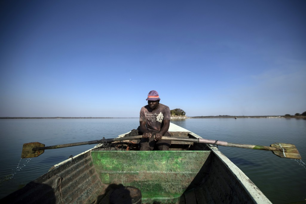 A fisherman rows his boat after casting his nets for the night, in Lake Chivero, west of the capital Harare, in Zimbabwe, Sept. 10, 2019. (AP Photo/Be...