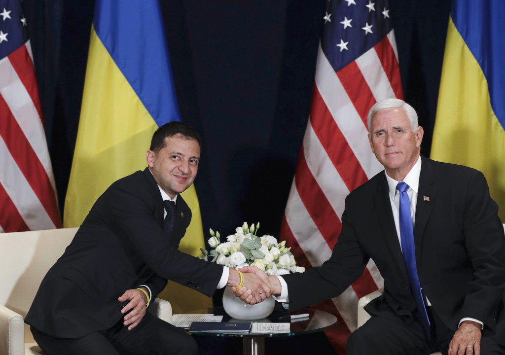 Ukraine's President Volodymyr Zelenskiy, left, shakes hands with U.S. Vice President Mike Pence, in Warsaw, Poland, Sunday, Sept. 1, 2019. (AP Photo/P