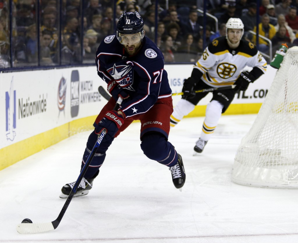 FILE - In this March 12, 2019, file photo, Columbus Blue Jackets forward Nick Foligno, left, controls the puck in front of Boston Bruins defenseman Br...