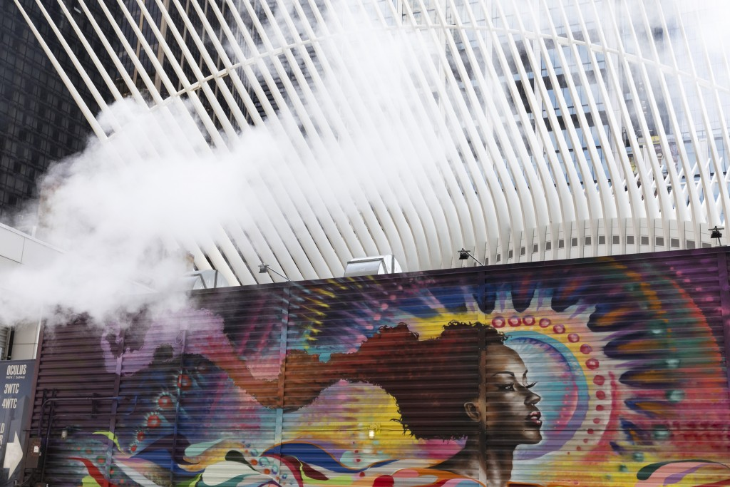 Steam blows by a mural placed at the future site of 2 World Trade Center, a planned commercial office tower, Monday, Sept. 9, 2019 in New York. In the