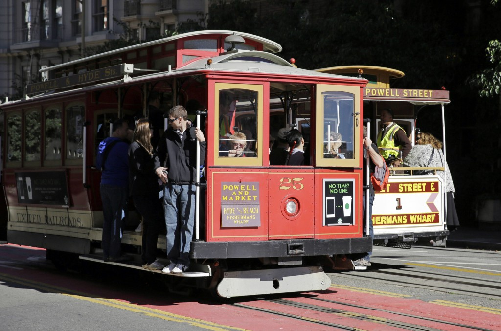 FILE - In this Nov. 3, 2015 file photo, a pair of cable cars go past each other on Powell Street atop Nob Hill in San Francisco. The city's iconic cab...