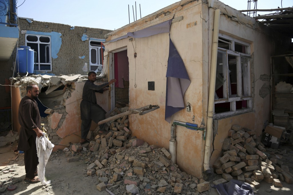 In this Tuesday, Sept. 10, 2019, photo, Afghans inspect their damaged house after a large explosion last week near a compound housing several foreign ...
