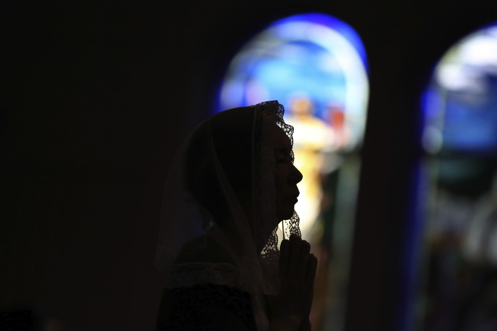 FILE - In this Aug. 9, 2015, file photo, a Catholic offers prayers at an early morning Mass to pay respect to the victims of the atomic bombing at the