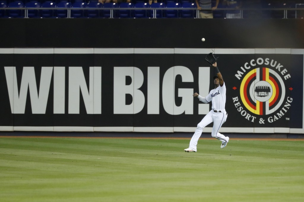 Miami Marlins center fielder Lewis Brinson catches a sacrifice fly by Milwaukee Brewers' Mike Moustakas during the first inning of a baseball game, Th...
