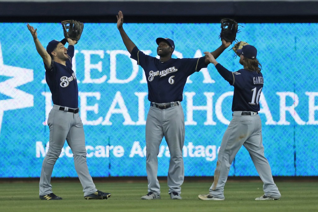 Milwaukee Brewers' Ryan Braun, left, Lorenzo Cain (6) and Ben Gamel (16) celebrate after they defeated the Miami Marlin during a baseball game, Thursd...