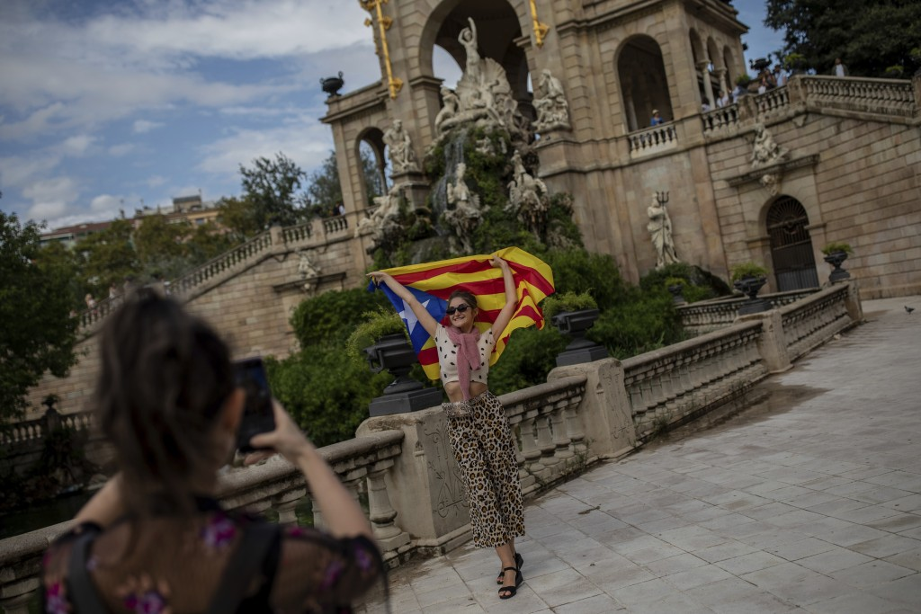 An Ukranian tourist poses for a snapshot with a Catalan independence flag during the Catalan National Day in Barcelona, Spain, Wednesday, Sept. 11, 20