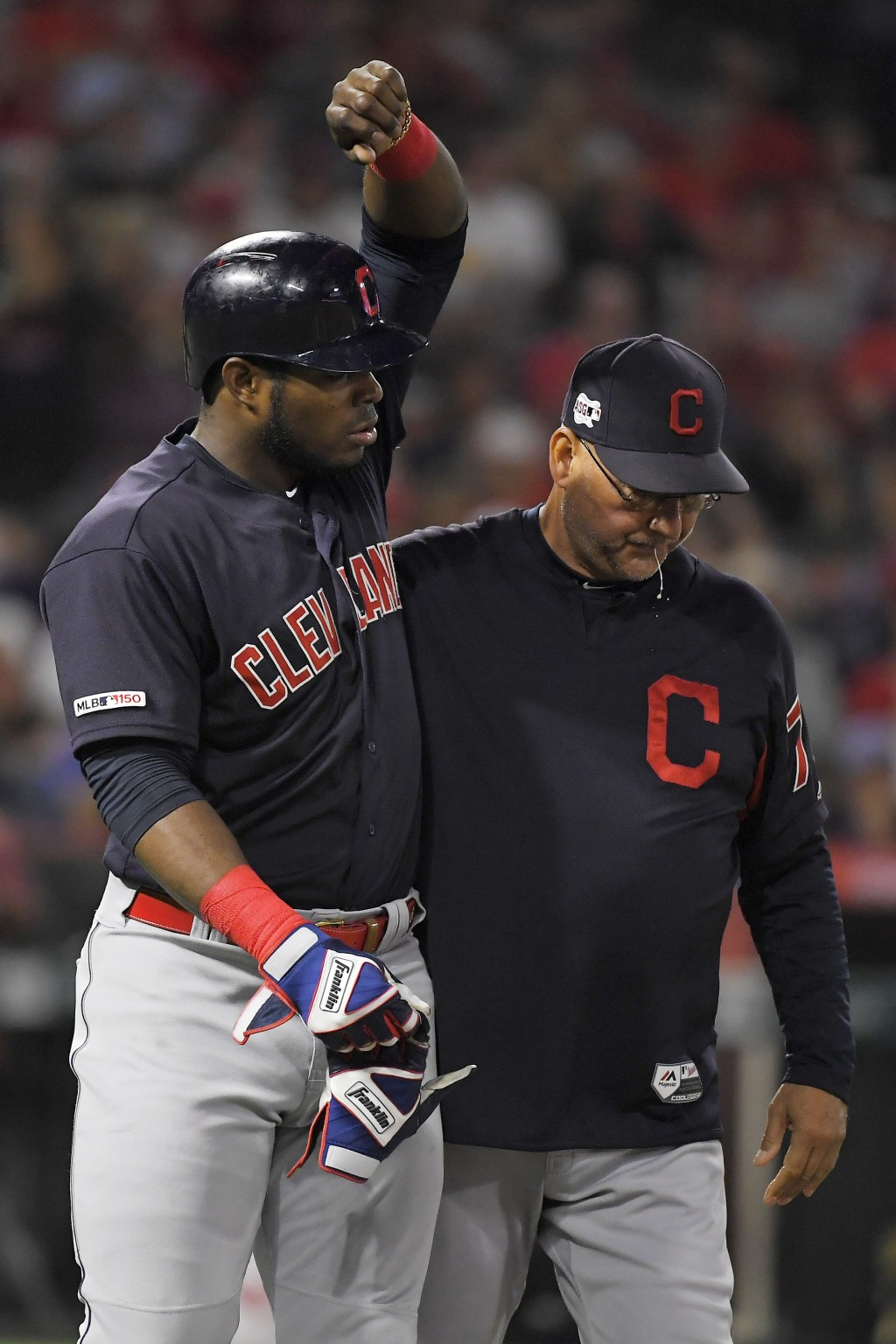 Cleveland Indians' Yasiel Puig, left, is accompanied by manager Terry Francona on the way to first after being hit by a pitch for the second time of t