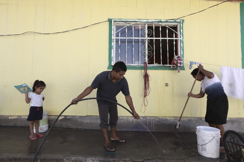 Central American migrants clean the Pan de Vida shelter for migrants in Ciudad Juarez, Mexico, where they are staying while waiting for a chance to re...