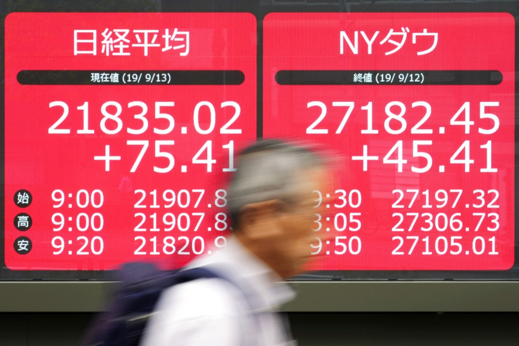 A man walks past an electronic stock board showing Japan's Nikkei 225 index at a securities firm in Tokyo Friday, Sept. 13, 2019. Stocks were broadly