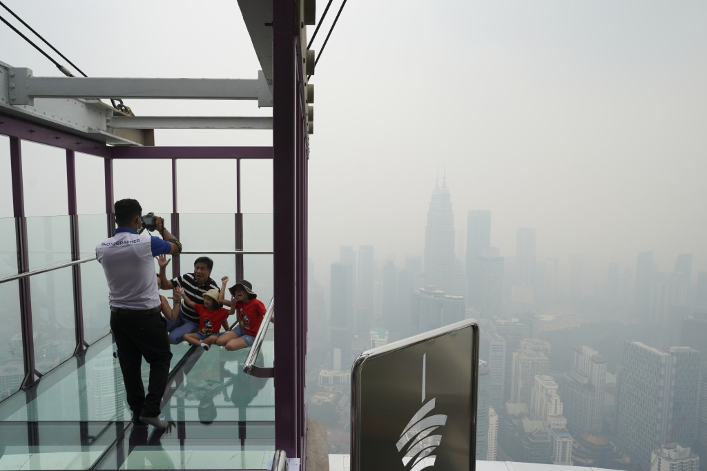 Tourists take a picture at Skybox of Kuala Lumpur Tower as city stands shrouded with haze in Kuala Lumpur, Malaysia, Friday, Sept. 13, 2019. Malaysian