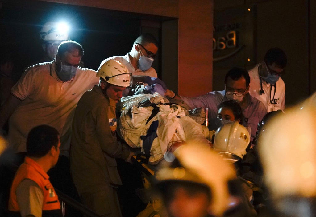 A patient is evacuated from a burning hospital in Rio de Janeiro, Brazil, Thursday, Sept. 12, 2019. The fire forced staff to hastily evacuate patients...