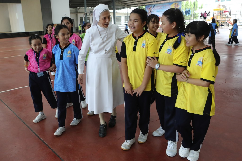 In this Aug. 27, 2019, photo, ST. Mary's School Vice Principal Sister Ana Rosa Sivori, center, talks to students during a lunch break at the girls' sc