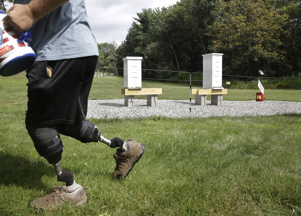 In this Aug. 7, 2019 photo, U.S. Army veteran Oscar Toce cleans up after beekeeping at the Veterans Affairs' beehives in Manchester, N.H. Veterans Aff...