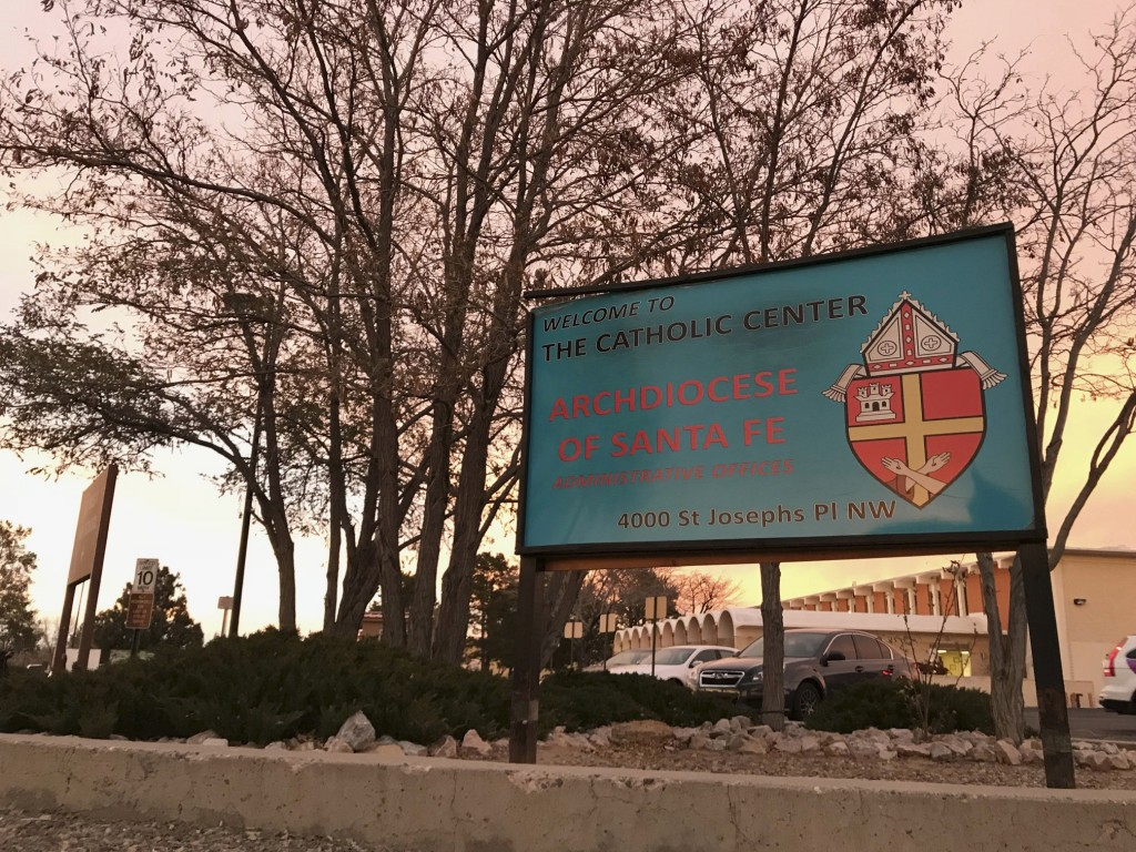 FILE - In this Nov. 29, 2018, file photo, the sun sets on a sign in front of the Archdiocese of Santa Fe offices in Albuquerque, N.M. A former Roman C
