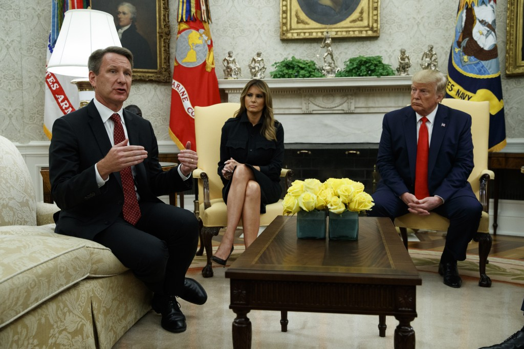 President Donald Trump and first lady Melania Trump listen as acting FDA Commissioner Ned Sharpless talks about a plan to ban most flavored e-cigarett...