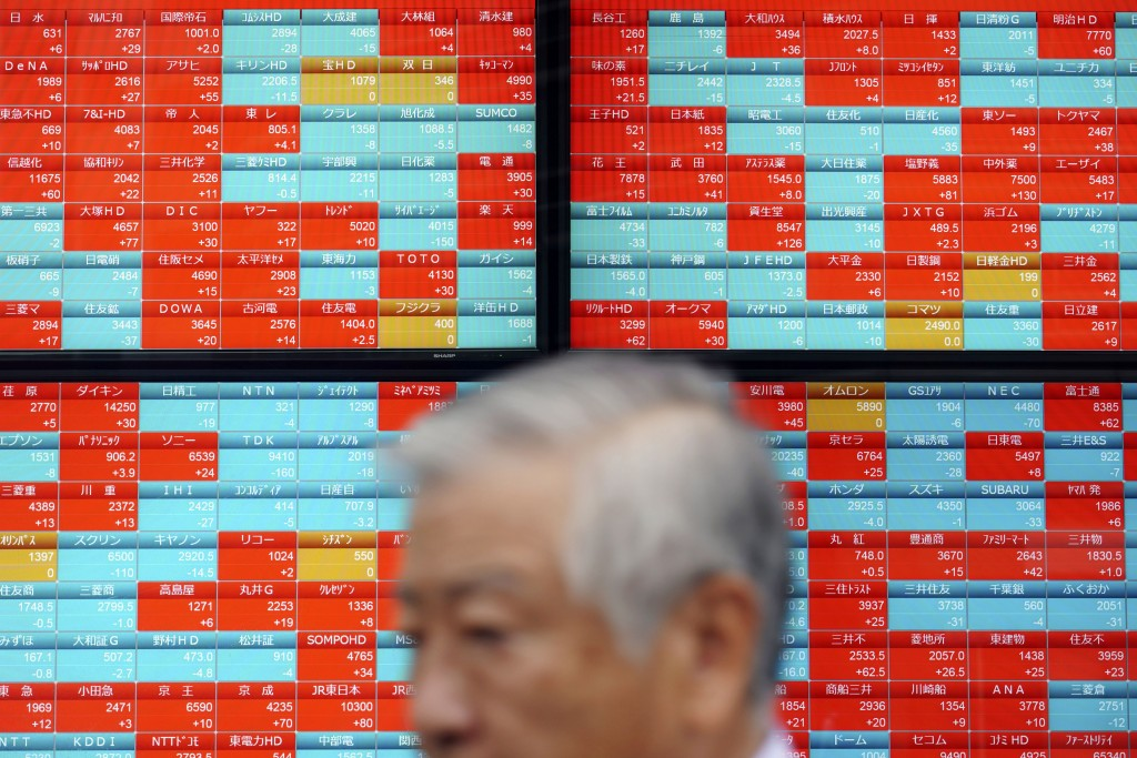 A man walks past an electronic stock board showing Japan's Nikkei 225 index at a securities firm in Tokyo Friday, Sept. 13, 2019. Stocks were broadly ...