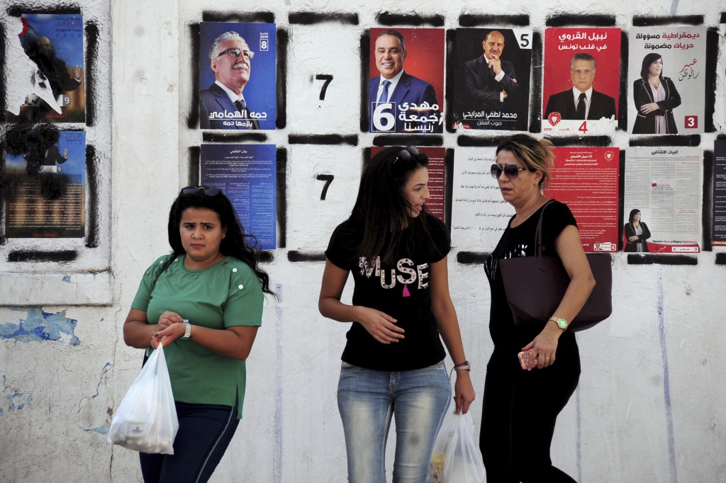 Women walk past candidates' posters and designated numbers a day before the start of presidential election in Tunis, Tunisia, Saturday, Sept. 14, 2019...