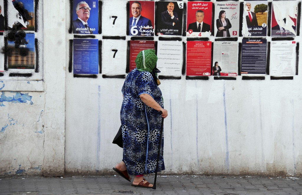 A woman pauses as she walks past candidates' posters and designated numbers a day before the start of presidential election in Tunis, Tunisia, Saturda