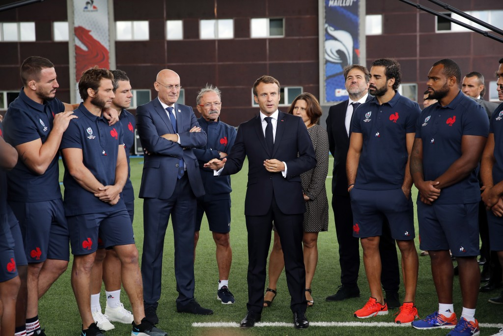 France's President Emmanuel Macron, center, speaks to French national rugby team players ahead of the upcoming Rugby Wcup, at the National Rugby Cente