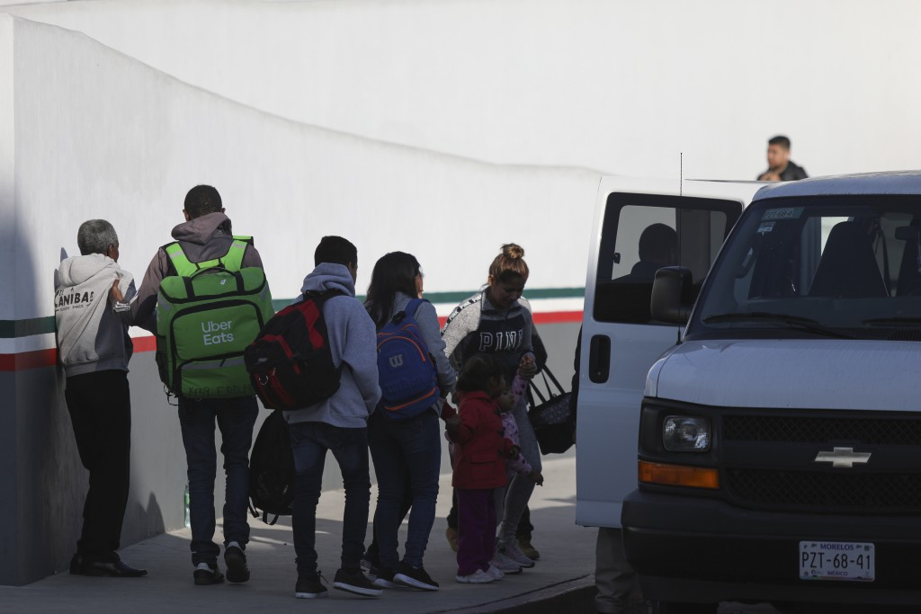 Ten migrants whose number from the waiting list was called, board a van to cross the border and apply for asylum in the United States, at the El Chapa...