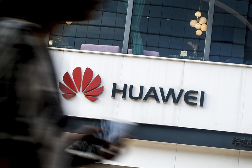 FILE - In this July 30, 2019, file photo a woman walks by a Huawei retail store in Beijing. The U.S. government gave chipmakers and technology compani
