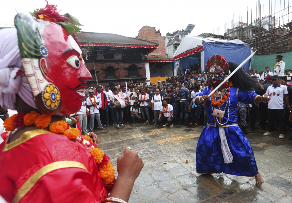Masked dancers perform a traditional dance during Indra Jatra festival, an eight-day festival that honors Indra, the Hindu god of rain, in Kathmandu,