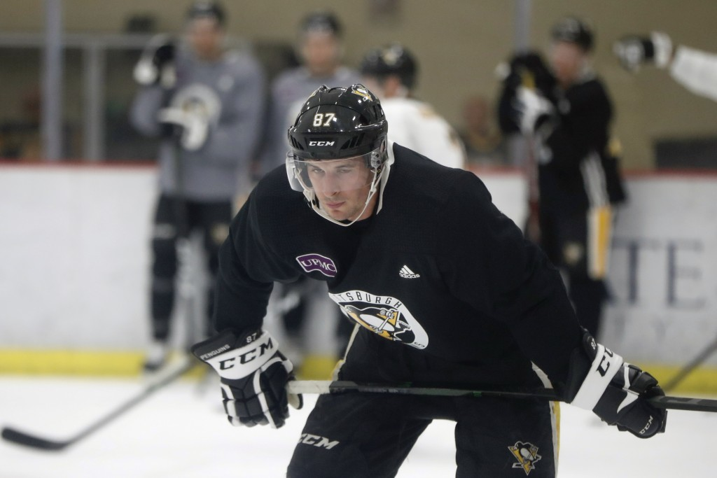 Pittsburgh Penguins' Sidney Crosby pauses before the start of a drill during NHL hockey practice on the team's first day of training camp, Friday, Sep...