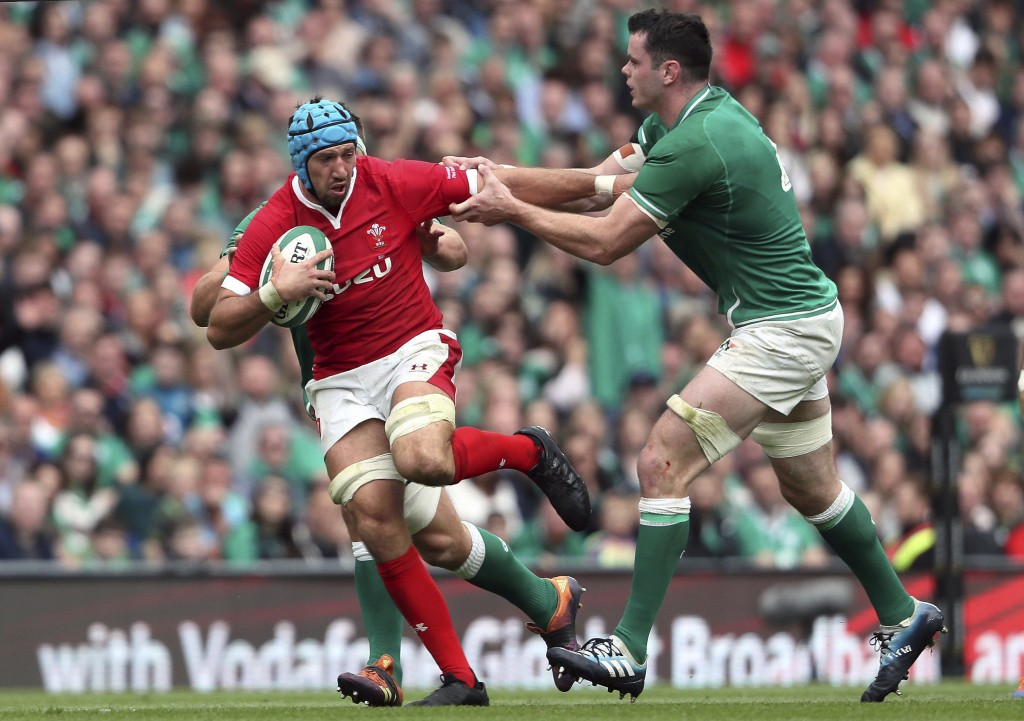 Wales' Justin Tipuric, left, is tackled by Ireland's James Ryan during the summer series rugby match between Wales and Ireland at the Aviva Stadium, D...