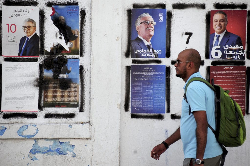 A man walks past candidates' posters and designated numbers a day before the start of presidential election in Tunis, Tunisia, Saturday, Sept. 14, 201...