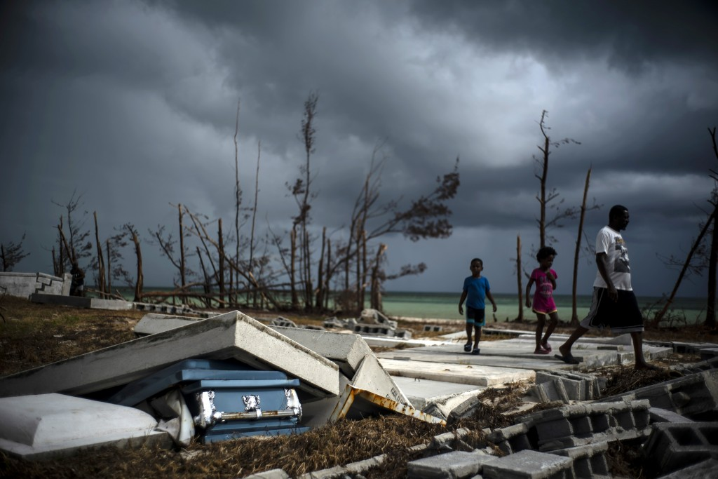 People walk next to a shattered and water-filled coffin lays exposed to the elements in the aftermath of Hurricane Dorian, at the cemetery in Mclean's...