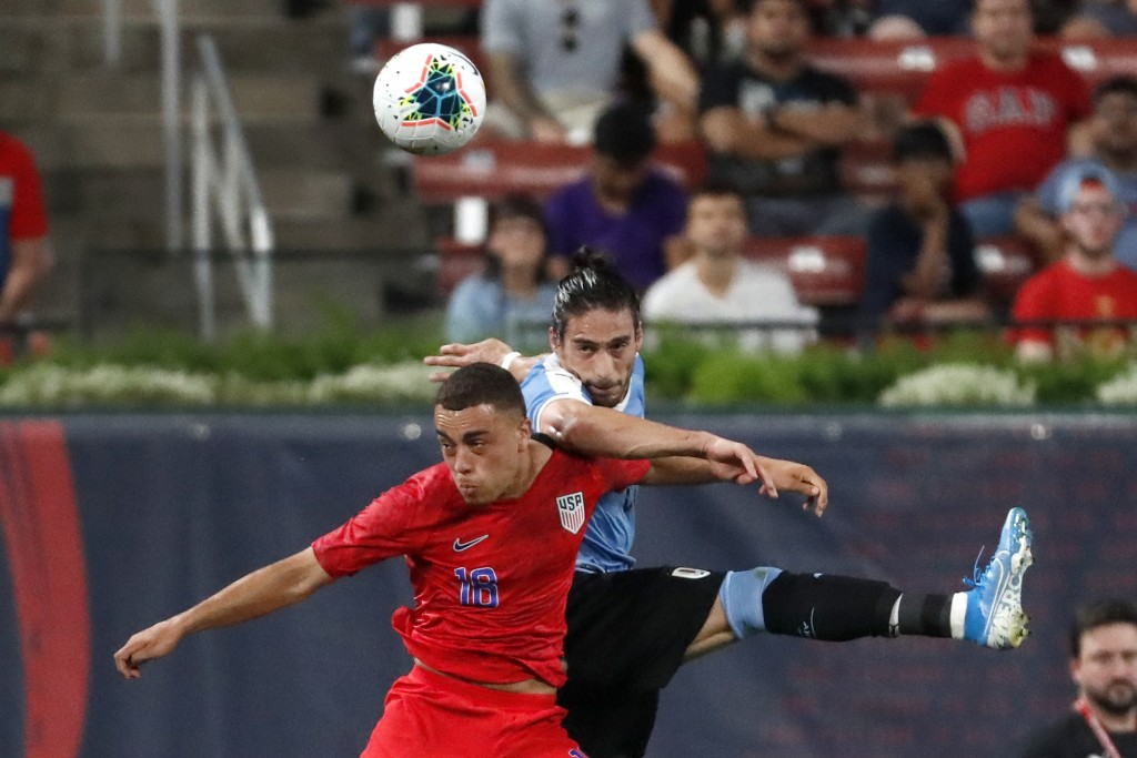 United States' Sergino Dest, left, and Uruguay's Martin Caceres leap after a loose ball during the first half of a friendly soccer match Tuesday, Sept...