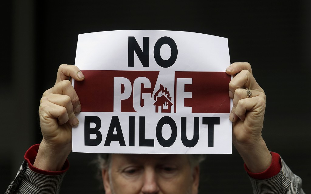 FILE - In this Monday, Jan. 28, 2019 photo, a man holds a sign at a rally before a California Public Utilities Commission meeting in San Francisco.  P