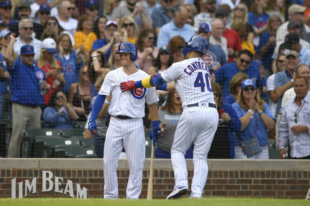 Chicago Cubs' Willson Contreras (40) celebrates with teammate Nico Hoerner left, after hitting a solo home run during the first inning of a baseball g