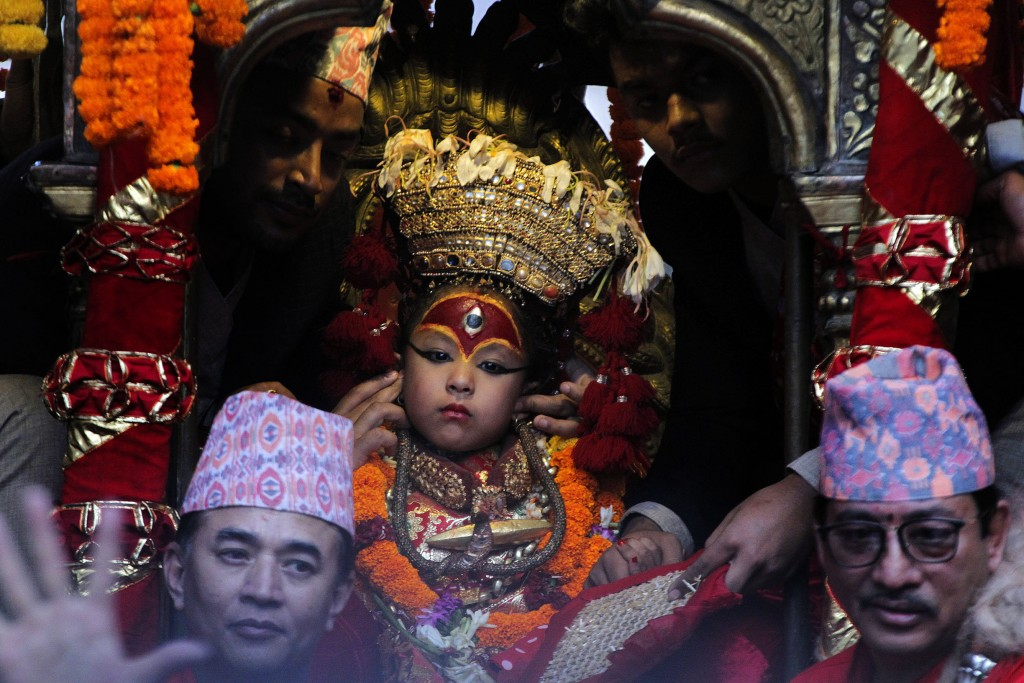 A priest covers the ears of living goddess Kumari as soldiers fire a gun as a part of rituals during Indra Jatra festival, an eight-day festival that