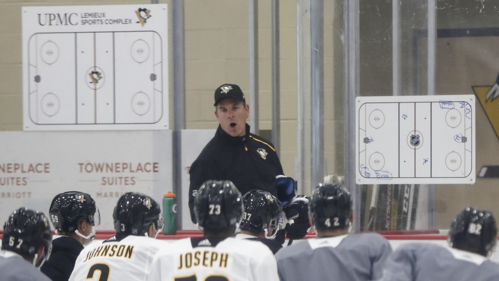 Pittsburgh Penguins coach Mike Sullivan, center, instructs the team on a drill during NHL hockey practice on the team's first day of training camp, Fr...
