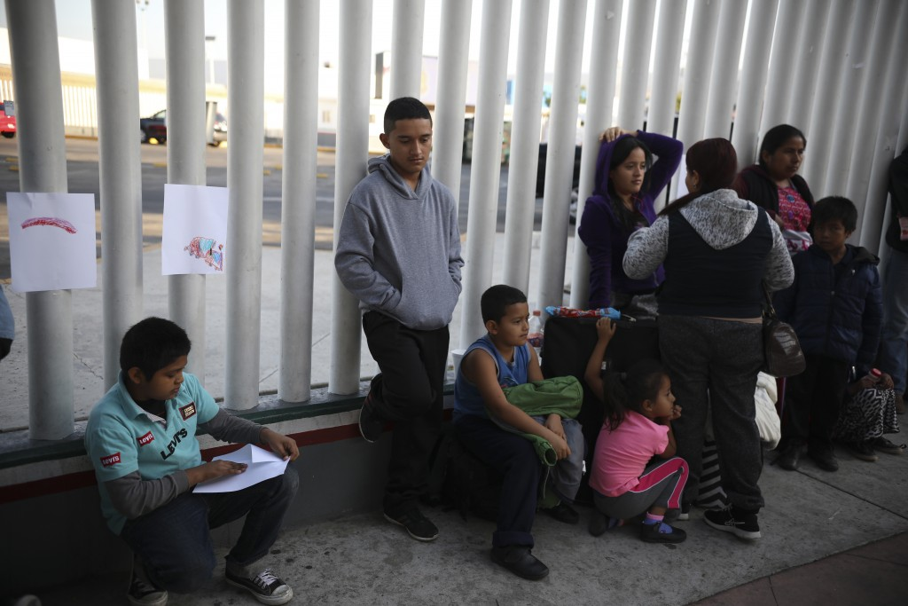 Central American migrants wait to see if their number will be called to cross the border and apply for asylum in the United States, at the El Chaparra...
